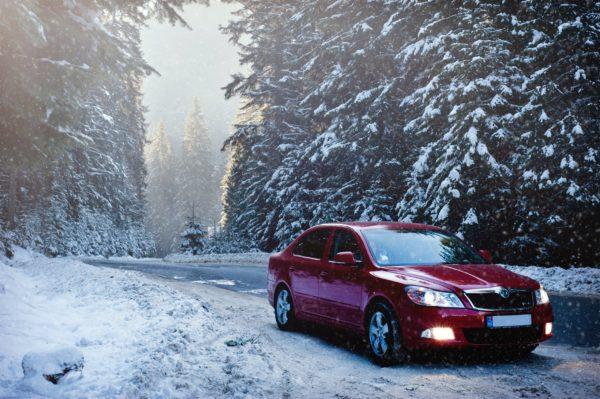 Red car driving in snowfall